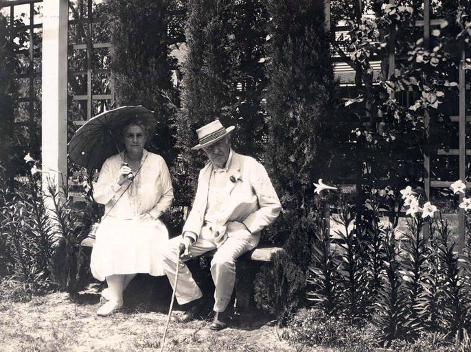 Mina and Thomas Edison on a bench in the Moonlight Garden around 1930. She holds a parasol and he holds a walking stick/cane.