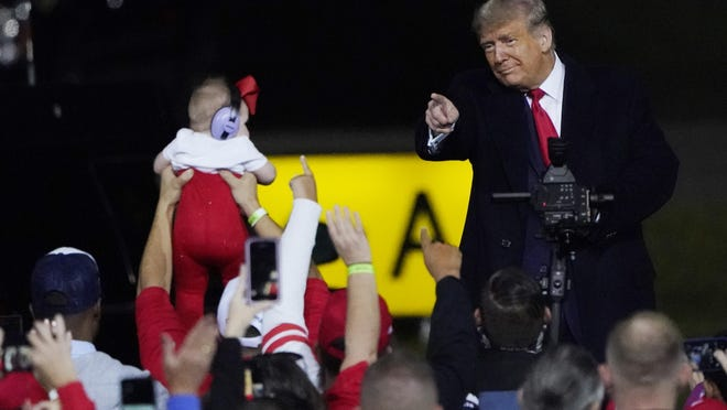 President Donald Trump wraps up his speech and points to an infant at a campaign rally at Fayetteville Regional Airport, Saturday, Sept. 19, 2020, in Fayetteville, N.C.
