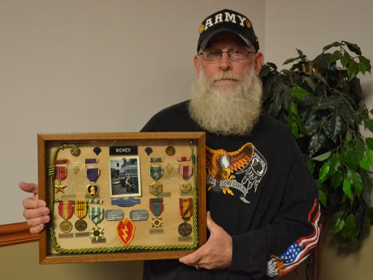Jerry Widmer holds the 11 medals he received during