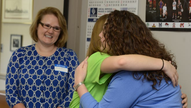 Teresa Kramer, left, watches as her daughter Krissy Kramer is congratulated by Lisa Bates of the Wayne County Foundation after learning Kramer is the winner of a Lilly Endowment Community Scholarship on April 9 at Richmond High School.