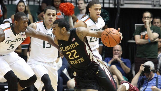 Xavier Rathan-Mayes tries to drive against the defense of University of Miami Davon Reed (5) and Angel Rodriguez (13) in the final seconds of the second half against Miami in Coral Gables, Fla.