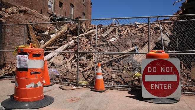 A Do Not Enter sign and orange markers sit outside the pile of debris at 17 and 19 Academy St. There are an estimated 5,000-6,000 tons at the site, according to Highground Industrial President David Hoehmann.