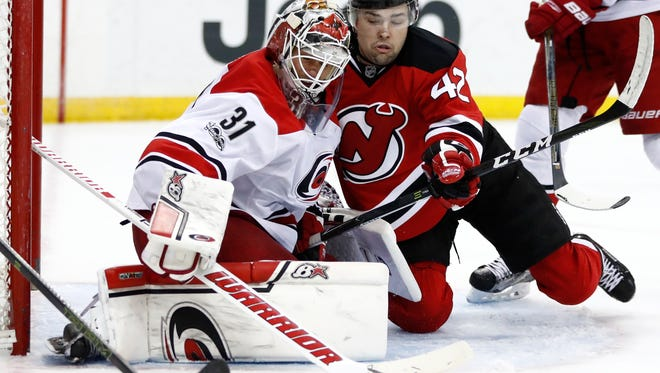 Carolina Hurricanes goalie Eddie Lack, left, of Sweden, and New Jersey Devils center John Quenneville collide as Lack deflects the puck during the second period of an NHL hockey game, Saturday, March 25, 2017, in Newark, N.J. (AP Photo/Julio Cortez)