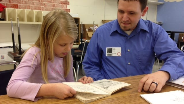 "Michael Perkins coaches a student from North Pointe Elementary in the ""One to One: Practicing Reading with Students"" program."