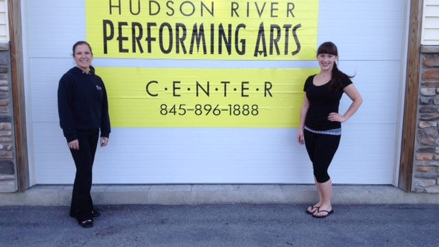 Dance studio owner Teresa Lawrence, left, and Shannon Herrmann stand by the arts center sign.