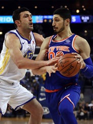 New York Knicks center Enes Kanter, right, drives the ball against Golden State Warriors center Zaza Pachulia (27) during the first half of an NBA basketball game Tuesday, Jan. 23, 2018, in Oakland, Calif. (AP Photo/Ben Margot)