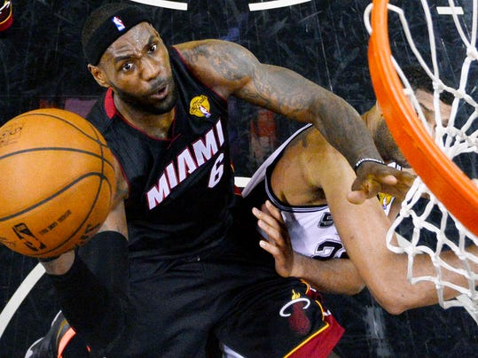 Miami Heat forward LeBron James shoots over San Antonio Spurs forward Tim Duncan (21) during the first half in Game 2 of the NBA basketball finals on Saturday, Nov. 8, 2014, in San Antonio. (AP Photo/Larry W. Smith, pool)