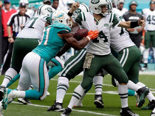 Dolphins' Cameron Wake knocking the ball loose while sacking Jets quarterback Ryan Fitzpatrick during the first half Sunday in Miami.