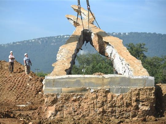 """A crane raises a 65-foot-tall sculpture Tuesday, Sept. 1, 2015 at the Sculpture Fields at Montague Park in Chattanooga, Tenn., as a tribute to honor the five military members who were slain in July. Artist Peter Lundberg created the sculpture, named """"Anchors."""""""