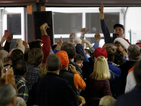 "Supporters of Donald Trump point out a protester and start chanting ""Trump, Trump, Trump"" while Republican presidential candidate, businessman Donald Trump, speaks during a rally coinciding with Pearl Harbor Day at Patriots Point aboard the aircraft carrier USS Yorktown in Mt. Pleasant, S.C., Monday, Dec. 7, 2015. Before the rally started the crowd was told what to do if protesters interrupted the speech."
