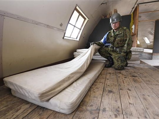 A member of the Self-Defense Force shows the mattress which Yamato Tanooka, a 7-year-old Japanese boy who went missing nearly a week ago, was using inside a building in a military drill area in Shikabe town, on Japan's northernmost main island of Hokkaido.