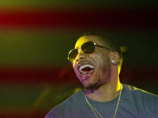 FILE - In this April 18, 2015, file photo, rapper Nelly laughs on stage during a Corner Block Party concert at Auburn University in Auburn, Ala. Nelly promised on Twitter Feb. 28, 2017, to bring baseball Hall of Famer Mike Piazza back to eat in the rapper's hometown of St. Louis after Piazza spoke ill of the city's restaurant scene.