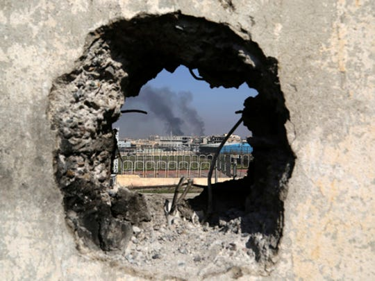Smoke rises from government complex, seen through a hole in a wall that made by Iraqi forces to fire their weapons, as Iraqi security forces advance during fighting against Islamic State militants in western Mosul, Iraq, Tuesday, March 7, 2017. U.S.-backed Iraqi forces were fighting their way through a government complex in the heart of western Mosul after storming the buildings in an overnight raid, and were facing fierce counterattacks Tuesday from the Islamic State group.