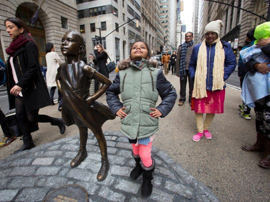 "Shriya Gupta of Cherokee, N.C. strikes a pose with a statue titled ""Fearless Girl"", Wednesday, March 8, 2017, in New York. The statue was installed by an investment firm in honor of International Women's Day."