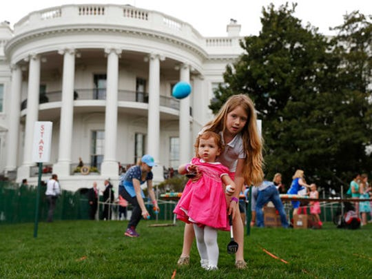 Eggs fly as Caroline Earnshaw, 10, helps her sister Brooke Earnshaw, 2, during the White House Easter Egg Roll on the South Lawn of the White House in Washington, Monday, April,17, 2017. President Donald Trump and first lady Melania Trump are set to host the official annual Easter egg roll at the White House.