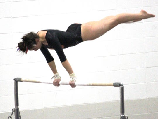 Northville freshman Maria Scavnicky competes on the uneven parallel bars in the KLAA meet.