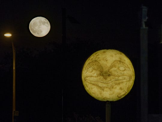 The full moon rises over the Man in the Moon sculpture