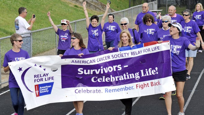 Hundreds participated in the 10th Annual American Cancer Society Relay for Life at Asheville High School Friday. Cancer survivors, from left to right, Kim Fisher, Charlotte Lail, Julie Young and Karen Chavez lead the first lap of the relay carrying the Relay for Life banner. Teams camp out to raise money for cancer research and local support services and in the evening light luminaries.