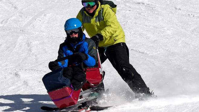 In this Feb. 22, 2018, photo, Bob Zahller guides Mickey Jones Jr. in a custom-built sled down a run at Whitefish Mountain Resort. The Disabled Recreation Environmental Access Movement program, or DREAM, has opened up recreation to hundreds of people with a wide variety of disabilities for the last 30 years.