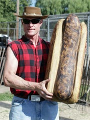 Kevin Salisbury of Sunfield, Michigan poses with a wooden brat he carved in anticipation of Brat Days Friday August 5, 2016 at Kiwanis Park in Sheboygan.