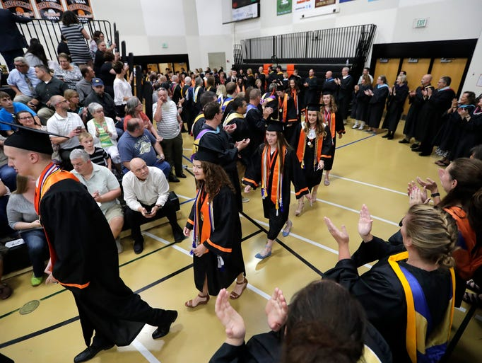 Students enter the fieldhouse to applauds from faculty