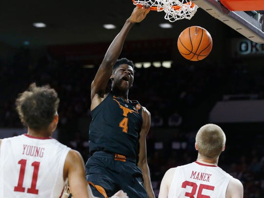 FILE - In this Feb. 17, 2018, file photo, Texas forward Mohamed Bamba (4) dunks in front of Oklahoma guard Trae Young (11) and forward Brady Manek (35) in the first half of an NCAA college basketball game, in Norman, Okla. Bamba was named to the AP All-Big 12 team, Tuesday, March 6, 2018. (AP Photo/Sue Ogrocki, File)