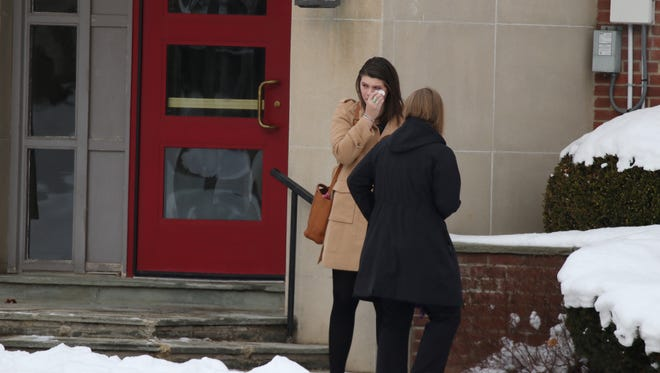 A mourner wipes tears after leaving funeral services for Kelsey Annese at Webster United Church of Christ on Klem Road.