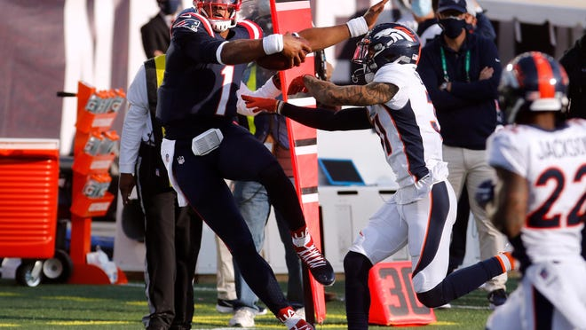 Patriots quarterback Cam Newton is knocked out of bounds by Broncos safety Justin Simmons after making a 16-yard reception on a fourth-quarter pass from Julian Edelman.