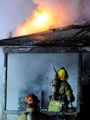 A Port Huron fire fighter vents the roof of the porch on a house fire late Thursday night in the 800 block of Port Huron.