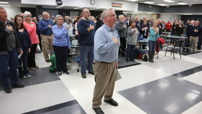 Warren County Republican chair Rick Halverson leads the Pledge of Allegiance before the start of a GOP precinct caucus on Feb. 1, 2016.