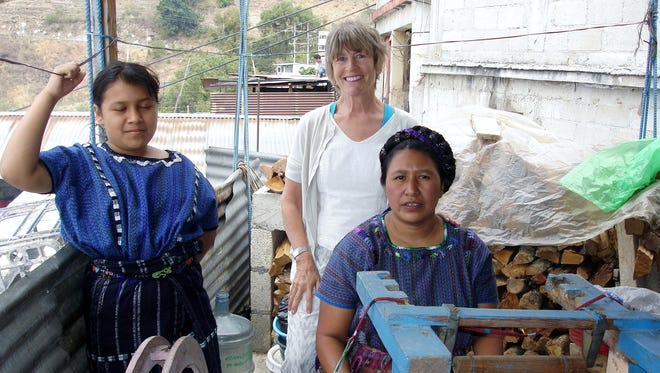"Wendy Carpenter of Interfibers Studio Gallery in Fish Creek, back, works with Florida, right, and Florida's daughter Jacquelyn in Lake Atitlan, Guatemala on a weaving project for Carpenter's ""Creating Revenue through the Arts"" mission in that country. Dresses made as part of the project are on a special holiday sale in the next week at Interfibers."