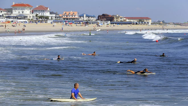 Surfers paddle out in the ocean in Loch Arbour. Views of the beachfront in Allenhurst in the background.