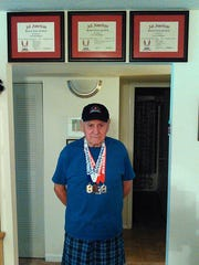 "Cory ""Sonny"" Hartbarger, formerly of Waynesboro, poses with his senior track and field medals and his All-American certificate in his home in Asheville, N.C."