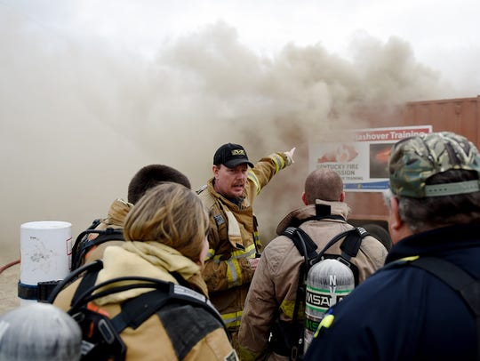 State Fire Rescue instructor Mark Boaz (center) points