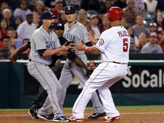 Los Angeles Angels' Albert Pujols is caught in a rundown at third, tagged out by Seattle Mariners pitcher Nick Vincent in a baseball game in Anaheim, Calif., Thursday, Aug. 18, 2016. The Angels won 6-4. (AP Photo/Reed Saxon)
