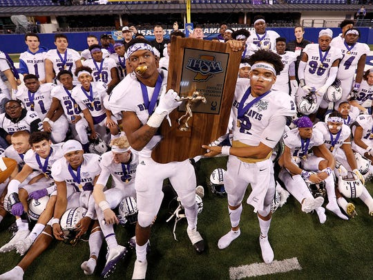 Ben Davis Giants Reese Taylor (2)  and  Keilan Laws (43) hold their championship trophy following their IHSAA 6A State Football finals game at Lucas Oil Stadium Saturday, Nov. 25, 2017. The Ben Davis Giants defeated the Penn Kingsmen  63-14.