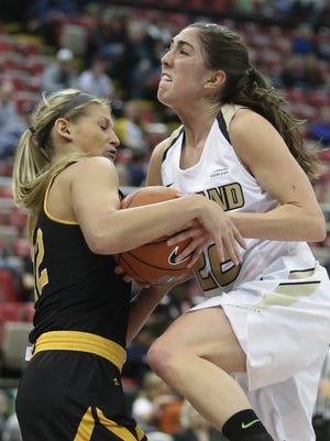 Oakland guard Taylor Gleason is tied up by Milwaukee guard Kelsey Cunningham during the first period of Oakland's 82-60 loss in the Horizon League tournament Sunday at Joe Louis Arena.