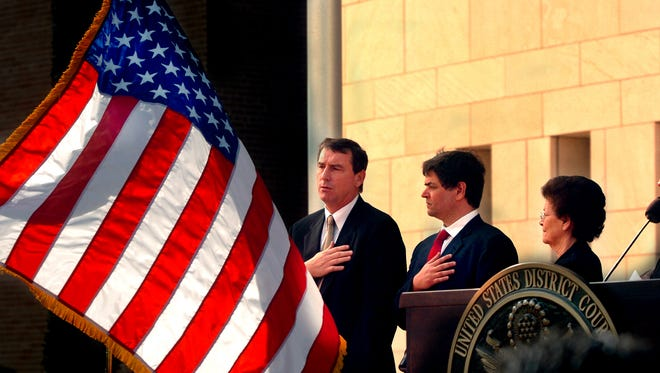 Judge Andrew Hanen, left, says the Pledge of Allegiance during a ceremony in Brownsville, Texas on Nov. 14, 2005. On Monday, Hanen blocked President Obama's executive action on immigration.