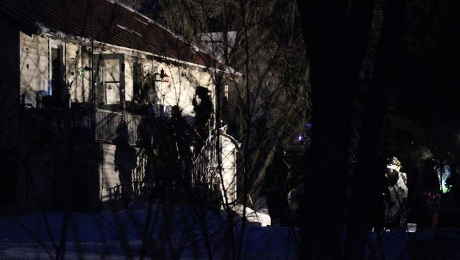 Firefighters can be seen at the back of a duplex in Mosinee, Thursday, February 12, 2015, as they work at the scene of a fire in which two persons died.