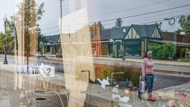 A reflection of the north side of East Washington Street in Irvington can be seen in the window of Leo Nguyen's new pho restaurant, currently under construction, on Monday, Sept. 11, 2017.