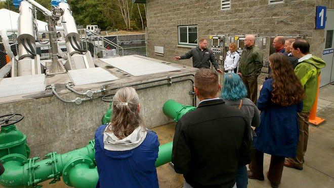 Kitsap Public Utility District treatment operator Luke Thurston, back center, leads a tour of the new Port Gamble wastewater treatment facility on Monday.