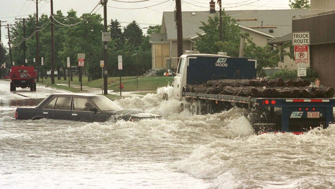 A semi trailer barrels down Union Avenue in Sheboygan creating huge waves for stranded vehicles Thursday, August 6, 1998, in Sheboygan, Wis. (FILE PHOTO)