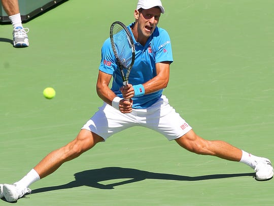 Novak Djokovic stretches for a shot during his victory over Andy Murray at the BNP Paribas Open, Saturday, March 21, 2015.