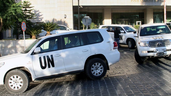 A convoy of chemical weapons disarmament experts departs the Four Seasons Hotel in Damascus, Syria, on Tuesday.