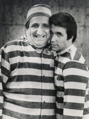 "In this photo provided by ABC in 1981, Al Molinaro, left, and Henry Winkler pose in character in an episode from ""Happy Days."""