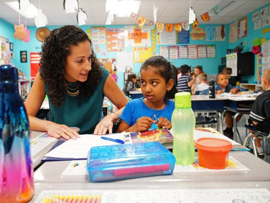 Danielle Rash, a third-grade inclusion teacher at Olive B. Loss, helps 8-year-old Advika Anand Muppavaram with an assignment.
