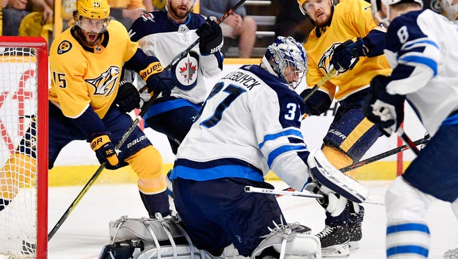 Winnipeg Jets goaltender Connor Hellebuyck (37) watches the puck as Nashville Predators right wing Craig Smith (15) and left wing Viktor Arvidsson (33) react during the first period of Game 7 of the second round NHL Stanley Cup Playoffs at Bridgestone Arena, Thursday, May 10, 2018, in Nashville, Tenn.