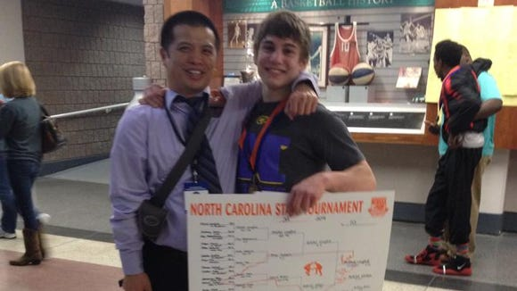 North Henderson wrestling coach Heang Uy, left, and Mitchel Langford.