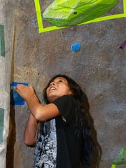 Ariana Perez, 11, eyes the last hold on her route during