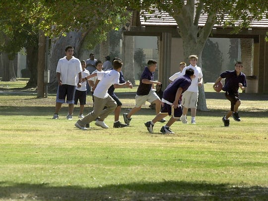 Kids from Indio Charter School take advantage of cool temperatures to play a game of football at the Miles Avenue Park.